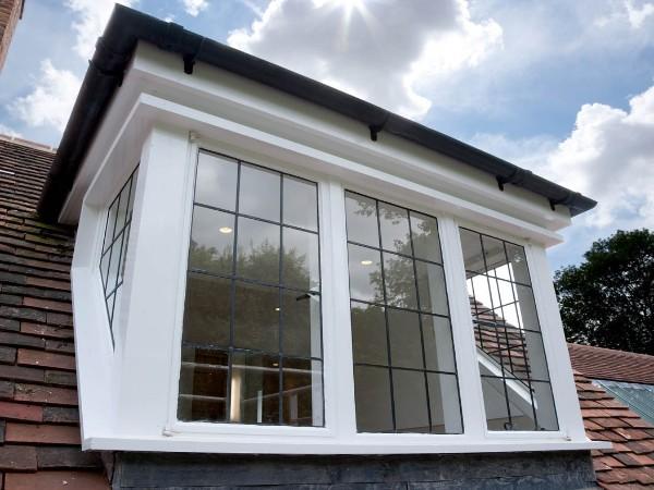 Eenvoudige glazen dakkapel met houten kozijnen, glazen zijkanten en voorkant